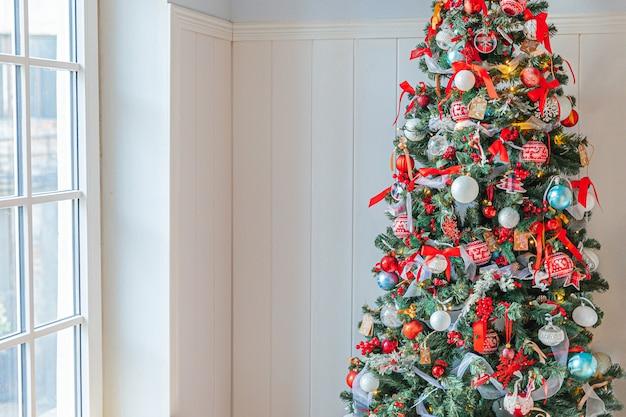 Klasyczna choinka z czerwono-białymi dekoracjami z zabawkami i piłką.