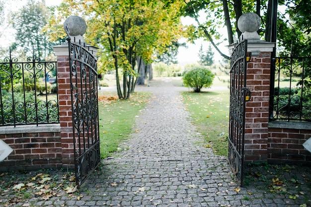 Klasyczna, czarna brama z kutego żelaza w pięknym zielonym ogrodzie.