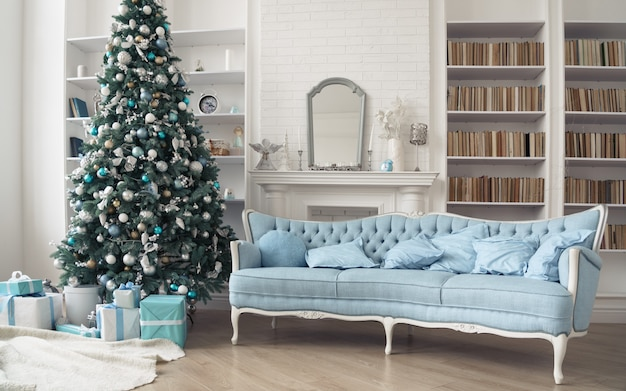 Klasyczna francuska niebieska sofa i ozdobiona choinka z pudełkami prezentowymi w salonie z półkami na książki