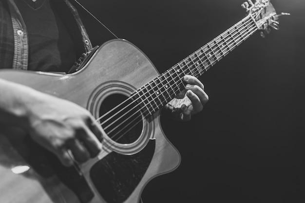 Klasyczna gitara akustyczna w rękach muzyka kopia przestrzeń.