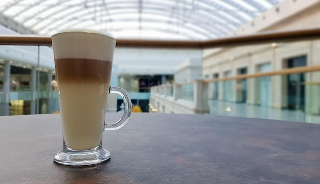 Klasyczna kawa latte macchiato w szklanej filiżance na stole. szklany kubek z gorącym napojem.