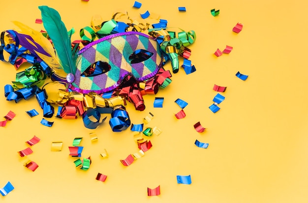Klasyczna kolorowa maska karnawałowa z piórami i konfetti na kolorowym tle.
