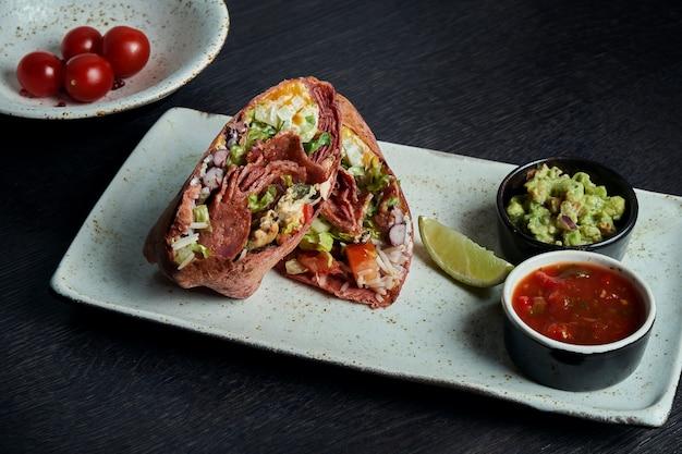 Klasyczna kuchnia meksykańska - burrito z małżami i chorizo, ryż, fasola w czerwonej tortilli na białym talerzu. smaczne z bliska. selektywne ustawianie ostrości. fast food. shawarma