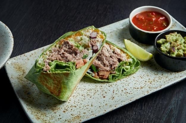 Klasyczna kuchnia meksykańska - burrito z wędzoną wieprzowiną, ryżem, fasolą w czerwonej tortilli na białym talerzu. smaczne z bliska. selektywne ustawianie ostrości. fast food. shawarma