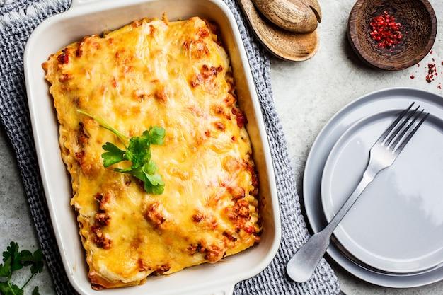 Klasyczna mięsna lasagne z serem w naczyniu piekarnika na jasnoszarym kolorze