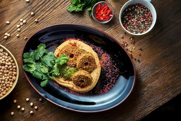 Klasyczna orientalna przekąska - hummus z ciecierzycy z falafelem, podawany na czarnym talerzu na drewnianym stole. jedzenie w restauracji