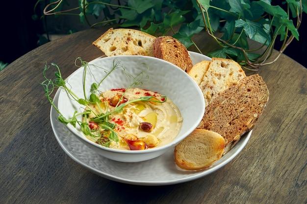Klasyczna orientalna przekąska - hummus z ciecierzycy z karmelizowanymi orzeszkami ziemnymi i grzankami w białym talerzu. selektywna ostrość