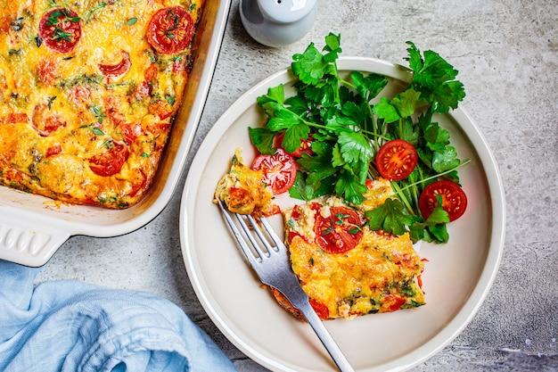 Klasyczna pieczona frittata lub omlet z pomidorami, papryką i serem na białym talerzu na jasnoszarym tle.