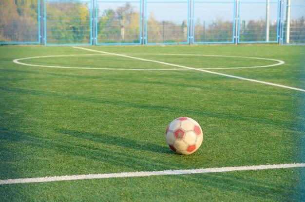 Klasyczna piłka na futbolowym zielonej trawy polu plenerowym. aktywny sport i trening fizyczny