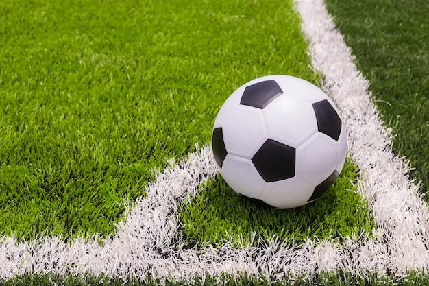 Klasyczna piłka na sztucznej jasnej i ciemnozielonej trawie