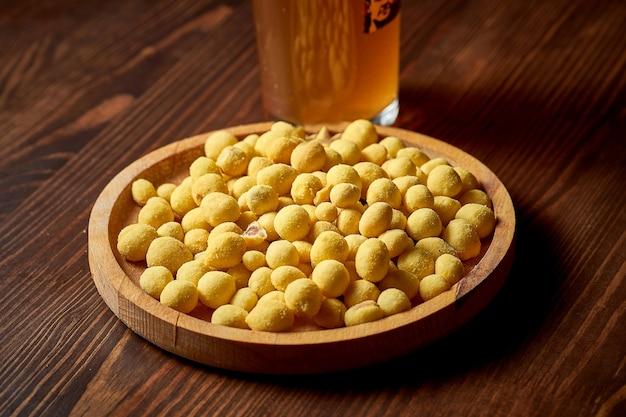 Klasyczna piwna przekąska to słone, prażone orzeszki ziemne na drewnianym talerzu. pub z jedzeniem