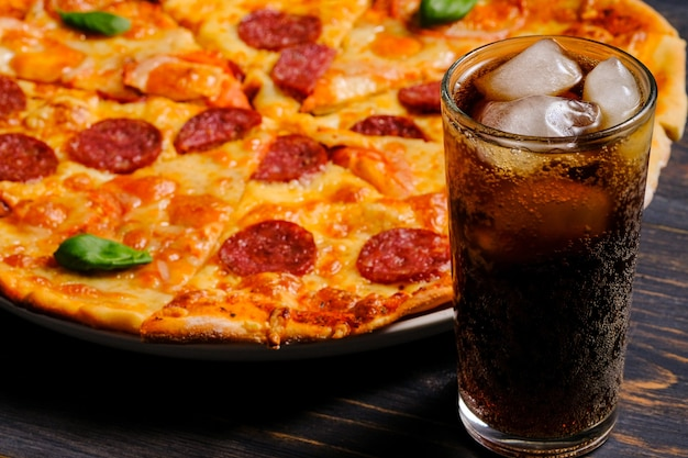 Klasyczna pizza pepperoni z serem w sosie pomidorowym i kiełbasą salami na czarnym drewnianym tle