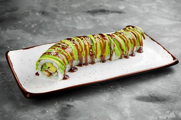 Klasyczna rolka sushi z zielonym smokiem z awokado, węgorzem, omletem i sosem unagi na białym talerzu na szarym stole. selektywna ostrość, ziarnistość szumu na słupku
