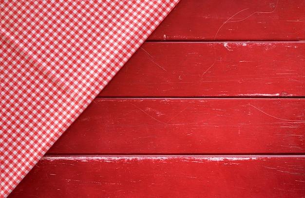Klasyczna różowa tkanina w kratę lub obrus na starym czerwonym stole z drewna z miejscem na kopię