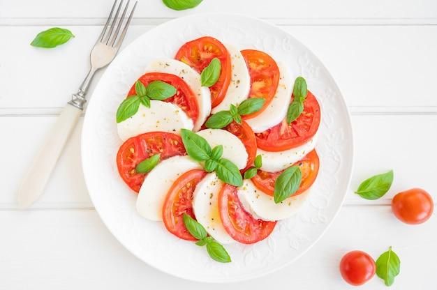 Klasyczna sałatka caprese z serem mozzarella, pomidorami i bazylią na białym talerzu
