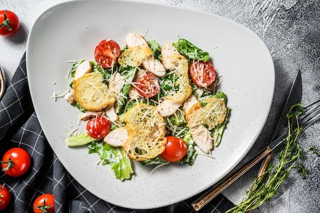 Klasyczna sałatka cezar z grillowaną piersią kurczaka, parmezanem, jajkami przepiórczymi, pomidorami i sałatą rzymską. białe tło. widok z góry