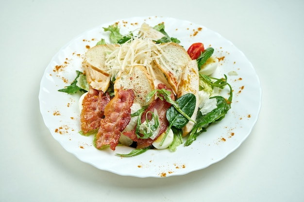 Klasyczna sałatka cezar z sałatą, szpinakiem, kurczakiem, grzankami, parmezanem i boczkiem w białym talerzu na białym talerzu