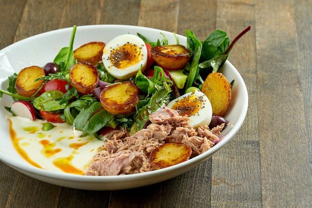 Klasyczna sałatka nicejska z gotowanym jajkiem, ziemniakami, tuńczykiem, oliwkami i białym sosem, podana w białej misce na drewnianym talerzu