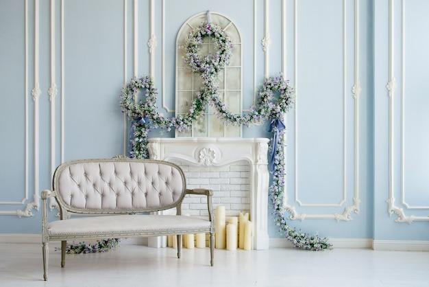 Klasyczna szara sofa w luksusowym białym pokoju. sztuczny kominek. na kominku. pokój ozdobiony jest kwiatami.