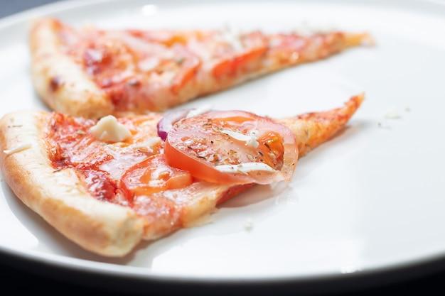 Klasyczna włoska pizza z pomidorami na białym talerzu