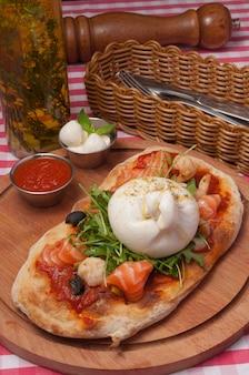 Klasyczna włoska pizza z serem buratta i łososiem