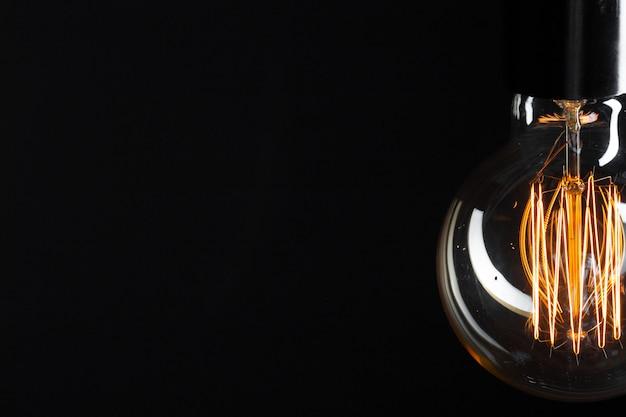 Klasyczna żarówka edisona w ciemności z miejscem na tekst