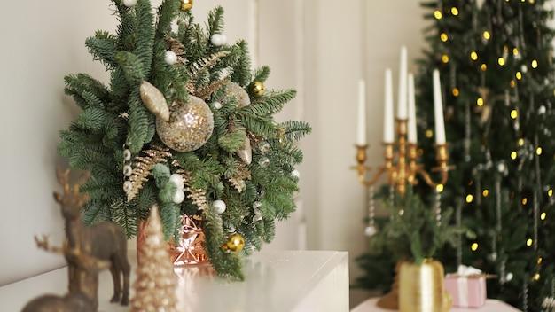 Klasyczne apartamenty z białym wnętrzem, dekorowanym drzewkiem, świecami, świątecznym wystrojem w kolorze złotym