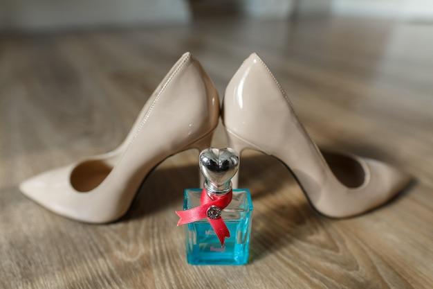 Klasyczne beżowe damskie buty na obcasie z bliska na drewnianej podłodze. modny zestaw ślubny - buty ślubne i perfumy. szczegóły ślubne