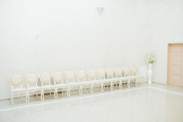 Klasyczne białe krzesła stoją w rzędzie w jasnym pokoju, przedpokoju