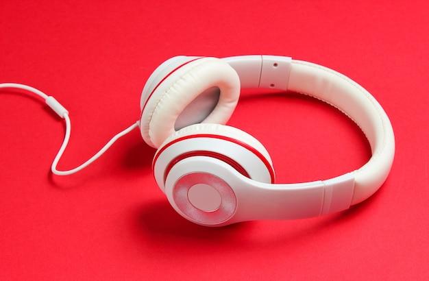Klasyczne białe słuchawki przewodowe na czerwonym tle papieru. styl retro. 80s. popkultury. meloman