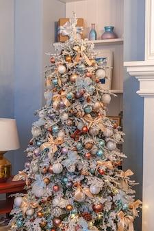 Klasyczne boże narodzenie nowy rok ozdobione choinką srebrną i białą ozdobą ozdoby zabawki i piłkę. nowoczesny apartament w stylu klasycznym. wigilia w domu.