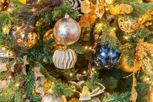 Klasyczne boże narodzenie nowy rok ozdobione nowy rok drzewo ze złotym ornamentem ozdoby zabawki i piłkę. nowoczesny biały apartament w stylu klasycznym. wigilia w domu