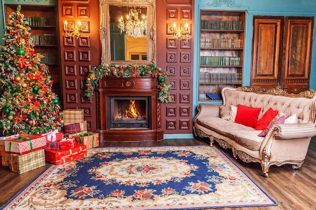 Klasyczne boże narodzenie nowy rok urządzone wnętrze pokoju domowa biblioteka z kominkiem. choinka z czerwonymi ornamentami. nowoczesny apartament w stylu klasycznym. wigilia w domu.