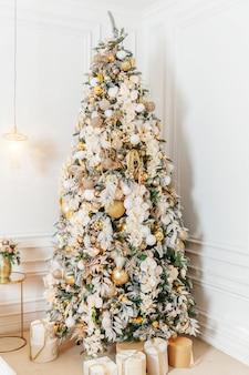 Klasyczne boże narodzenie nowy rok urządzone wnętrze pokoju drzewo nowego roku. choinka z dekoracjami złotymi ornamentami. nowoczesny biały apartament w stylu klasycznym. wigilia w domu.