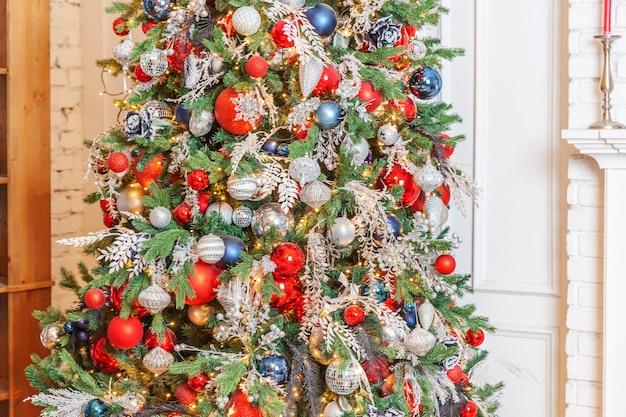 Klasyczne boże narodzenie nowy rok urządzone wnętrze pokoju drzewo nowego roku. choinka z ozdobami w kolorze srebrnym i czerwonym. nowoczesny biały apartament w stylu klasycznym. wigilia w domu