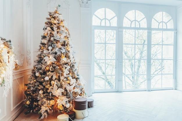 Klasyczne boże narodzenie nowy rok urządzone wnętrze pokoju drzewo nowego roku. choinka ze złotymi dekoracjami. nowoczesne białe mieszkanie w stylu klasycznym, duże okno. wigilia w domu.