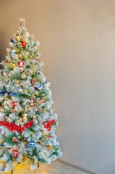 Klasyczne boże narodzenie zdobione drzewo nowy rok czerwony niebieski i biały ornament zabawka i piłka na tle szarej ściany. nowoczesny apartament w stylu klasycznym. wigilia w domu. skopiuj miejsce.