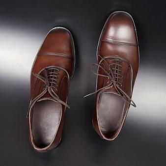 Klasyczne brązowe buty męskie na ciemnej podłodze