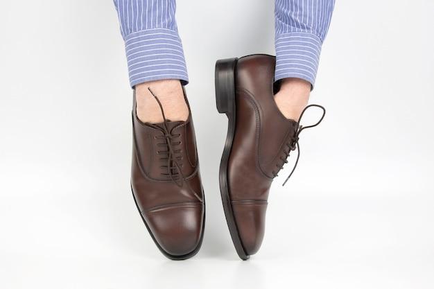 Klasyczne brązowe buty noszone na rękach na białym tle