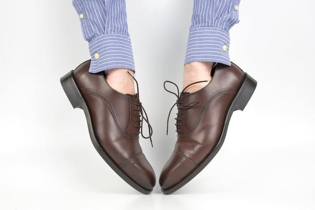 Klasyczne brązowe buty zakładane na ręce na biało
