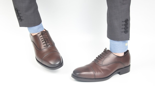 Klasyczne brązowe skórzane buty noszone na rękach na białej powierzchni