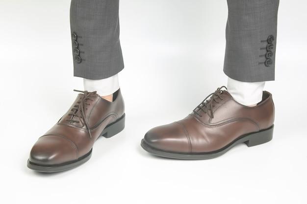 Klasyczne brązowe skórzane buty noszone na rękach na białym