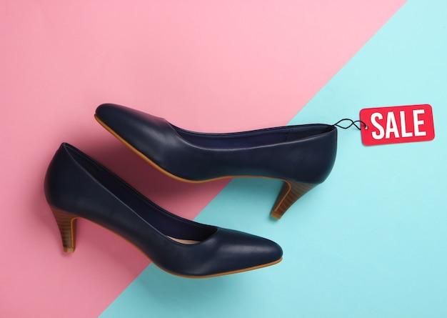 Klasyczne buty na obcasie z czerwoną metką wyprzedaży na różowo-niebieskim. wielka wyprzedaż, rabaty.