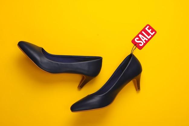 Klasyczne buty na obcasie z czerwoną metką wyprzedaży na żółtym tle. wielka wyprzedaż, rabaty