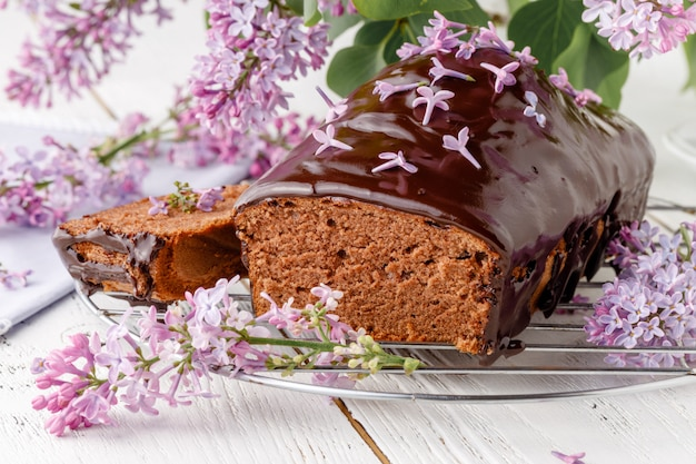 Klasyczne ciasto czekoladowe na białym stole z kwiatami