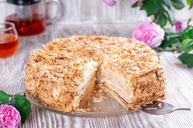 Klasyczne ciasto napoleona z filiżanką herbaty. tradycyjny deser millefeuille z ciasta francuskiego i kremu, przysmak kuchni rosyjskiej