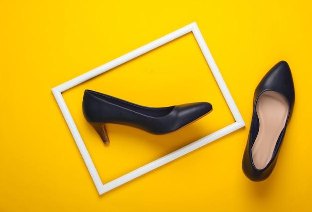 Klasyczne damskie buty na wysokim obcasie na żółtej powierzchni z białą oprawą