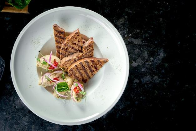 Klasyczne danie kuchni izraelskiej - śledź forszmak z grzankami podawany na białym talerzu na marmurowym stole. owoce morza.