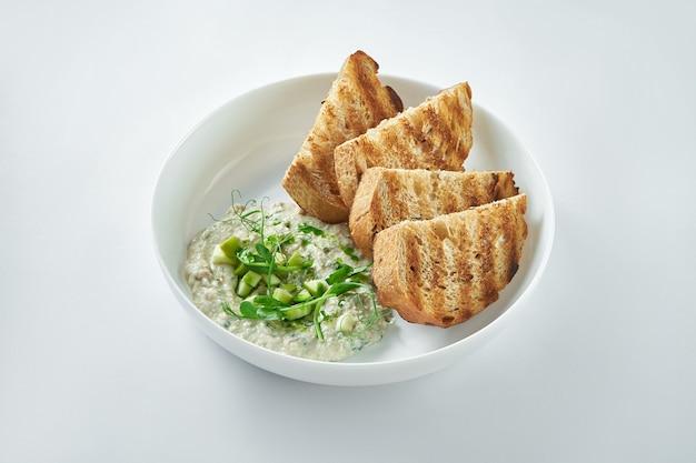 Klasyczne danie kuchni izraelskiej - śledź forszmak z grzankami w białym talerzu na białym talerzu
