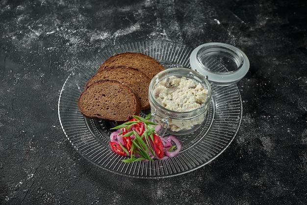 Klasyczne danie kuchni izraelskiej - śledź forszmak z grzankami w talerzu na ciemnym talerzu